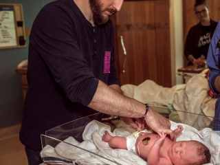 Birth Photography - Birth Photographer - dad taking care of newborn baby