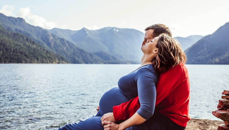 Maternity Photography - Maternity Photographer - Woman in blue dress cuddled into her husband by the water