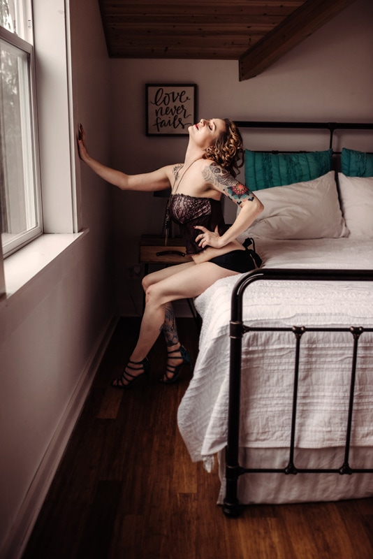 Boudoir Photography - Boudoir Photographer - Woman sitting on bed with hand on the wall