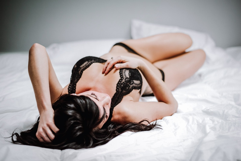 Boudoir Photography - Boudoir Photographer - Woman laying on white bedding in black lace