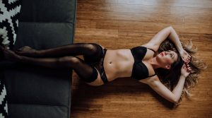 Boudoir Header - Ashley Grimes Photography - Woman laying on floor with feet up on couch